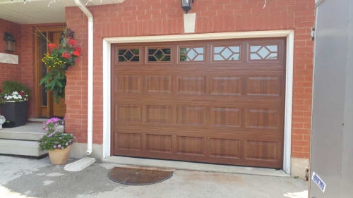 Brown garage door with windows installed on a property by Pro Entry Garage Doors
