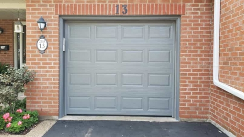 Grey single-car modern garage door without windows installed in Oakville by Pro Entry