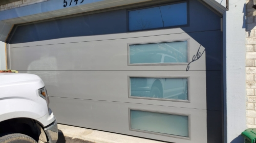 Modern garage door with glass panels installed by Pro Entry Services